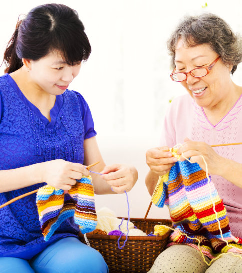 caregiver and senior woman sewing