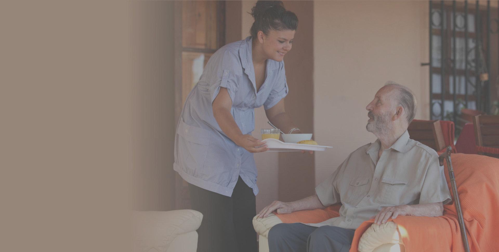 Caregiver giving food to a senior elderly