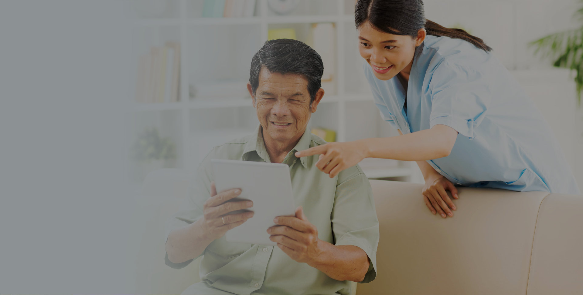 Caregiver teaching senior how to use a tablet