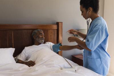 doctor measuring blood pressure of senior man in bedroom at home