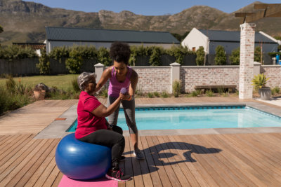 trainer training senior women in performing exercise on a swiss ball next to the swimming pool in the backyard of home