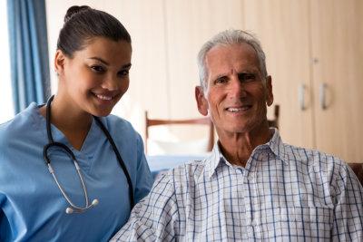 smiling female doctor with senior men sitting in nursing home