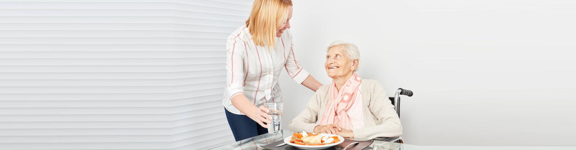 caregiver and elderly having a meals