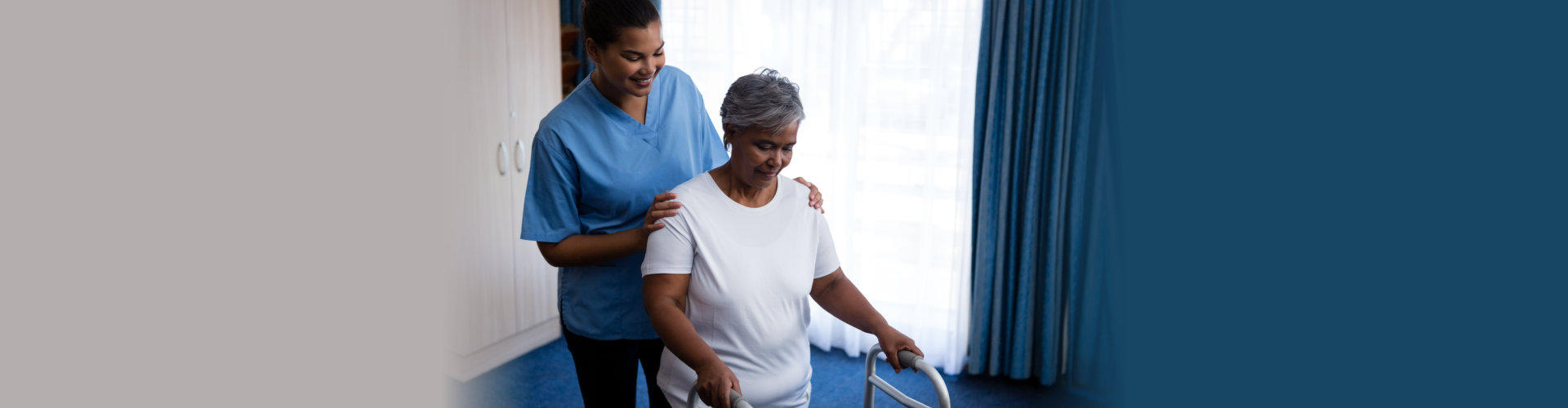 Nurse hepling senior women in walking with walker at nursing home